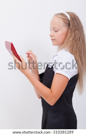 Portrait of teen girl with calculator over white background - stock photo