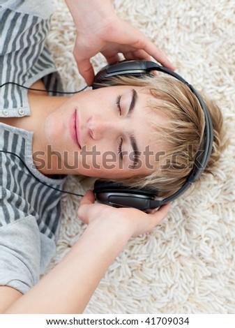 Portrait of teen guy listening to music with headphones - stock photo