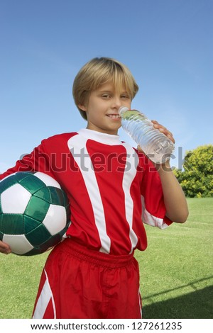 Portrait of teenage boy drinking water at field - stock photo