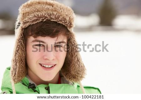 Portrait Of Teenage Boy In Snow Wearing Fur Hat - stock photo