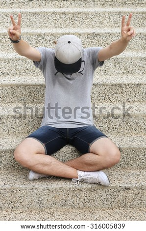Portrait of teenage boy showing victory symbol at the camera. - stock photo