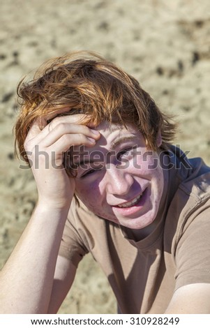 portrait of teenage boy with red hair at the beach - stock photo