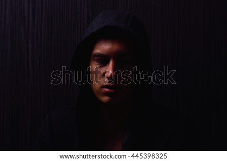Portrait of teenage boy with serious expression and black hoodie on his head, brown dark hair, direct gaze. Dark background, lights and shadows - stock photo