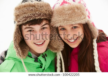 Portrait Of Teenage Couple In Snow Wearing Fur Hats - stock photo