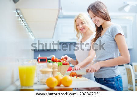 Portrait of teenage girl and her mother on background cooking in the kitchen - stock photo