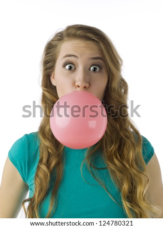 Portrait of teenage girl blowing a bubble gum against white background - stock photo