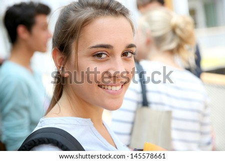 Portrait of teenage girl holding notebooks at school