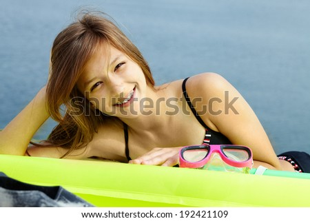 Portrait of teenage girl in bikini lying on mattress and looking at camera - stock photo