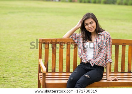 Portrait of teenage girl on bench in library - stock photo