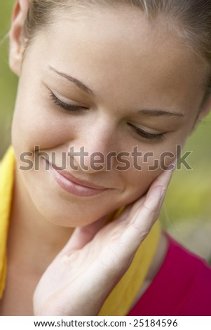 Portrait Of Teenage Girl Resting Head In Hands And Smiling