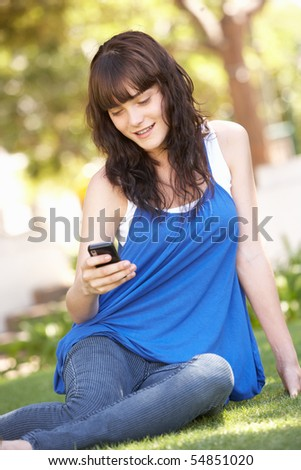 Portrait Of  Teenage Girl Sitting In Park Using Mobile Phone