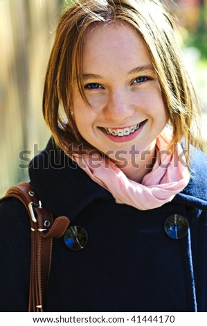 Portrait of teenage girl smiling wearing coat and scarf - stock photo