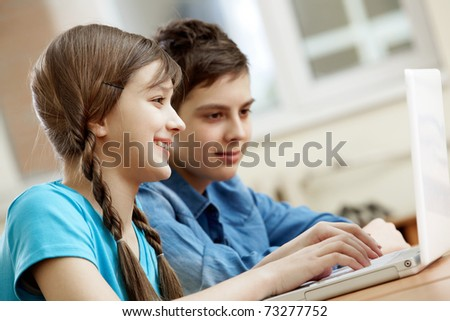 Portrait of teenage girl typing with her classmate at background - stock photo
