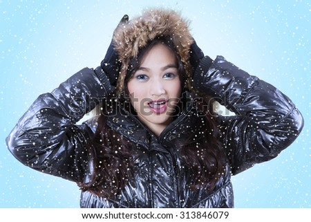 Portrait of teenage girl wearing winter clothes and looking on the camera against blue background