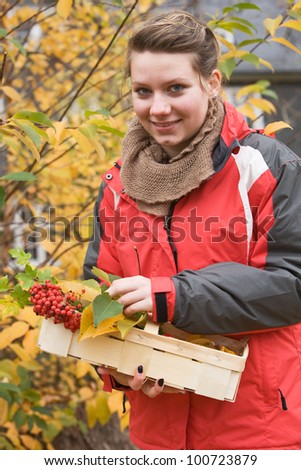 Portrait of teenage girl with basket of autumn leaves and berries - stock photo