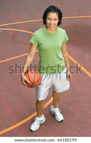 Portrait of teenage girl with basketball on court