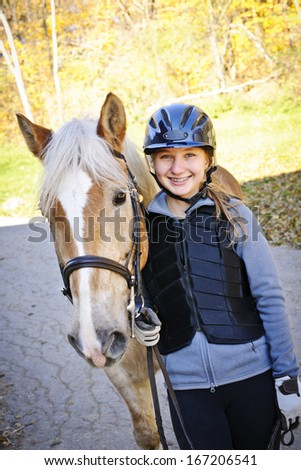 Portrait of teenage girl with horse outdoors on sunny day - stock photo
