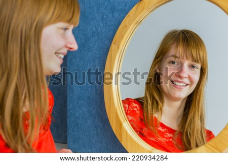 Portrait of teenage girl with red hair looking in mirror