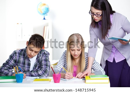 Portrait of teenage lad and girl writing somethinig during lesson while teacher checking their notes - stock photo