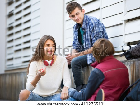 Portrait of teenage males and girl talking in autumn day outdoor - stock photo