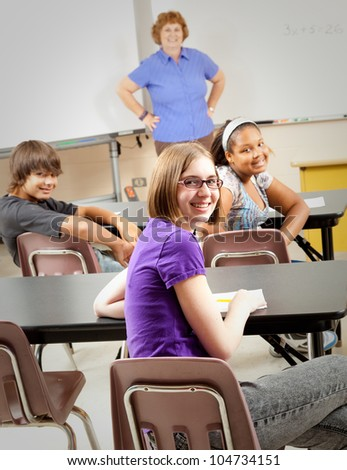 Portrait of teenage students and their teacher in the classroom.  Focus on the girl in the front with glasses. - stock photo