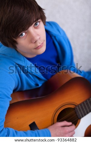 Portrait of teenager boy playing the guitar and dreaming away - stock photo