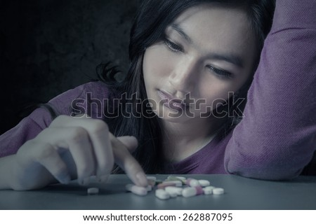 Portrait of teenager girl choosing pills with stressful expression, symbolizing a drugs addict - stock photo