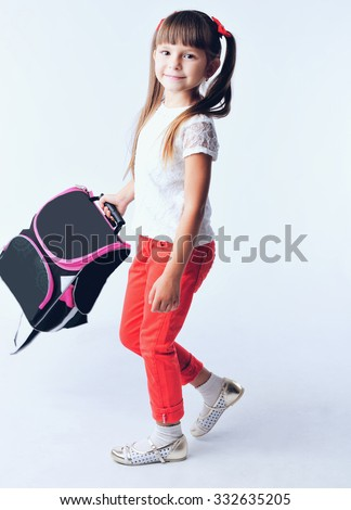Portrait of teenager girl with school backpack holding colored folders isolated on white background
