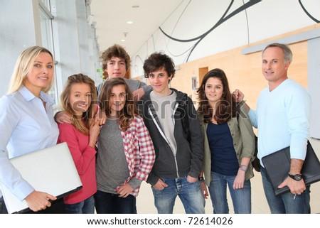 Portrait of teenagers and teachers standing on school hall - stock photo