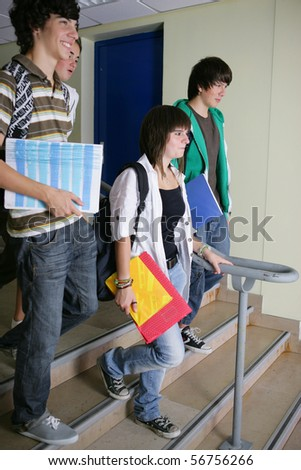 Portrait of teenagers coming down stairs holding documents