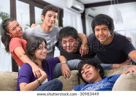 Portrait of teenagers from different races pose together at home showing their togetherness - stock photo