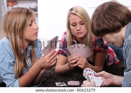 portrait of teenagers playing cards - stock photo