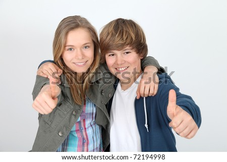 Portrait of teenagers with thumbs up - stock photo