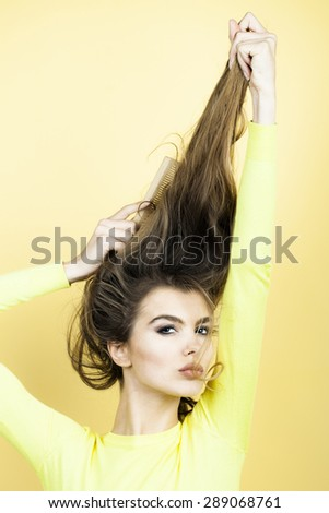 Portrait of tempting pretty young woman with long hair in yellow blouse looking forward combing hair with brush  standing on yellow background, vertical picture - stock photo