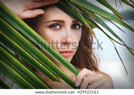 portrait of tender woman looking through palm leaf - stock photo