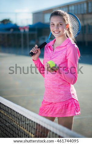 Portrait of tennis player with racket and ball.