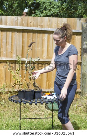 Portrait of terrified girl with shrunken plants in garden - stock photo