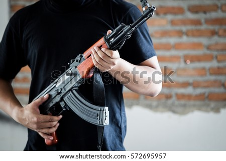 Portrait of terrorist holding assalt riffle close up.