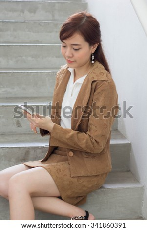Portrait of thai adult businesswoman beautiful girl using her smart phone.