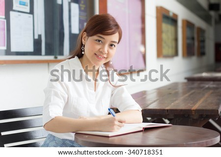 Portrait of thai adult businesswoman beautiful girl write a book.