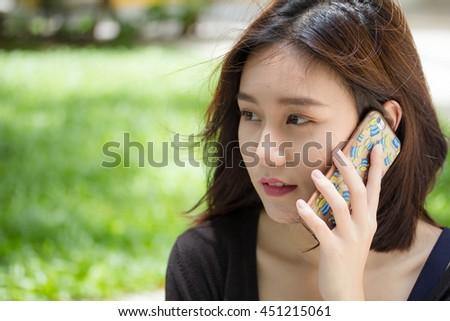 Portrait of thai adult student university beautiful girl calling smart phone - stock photo