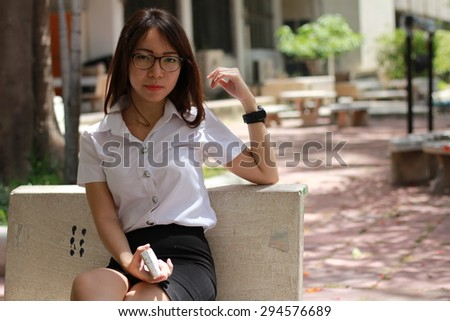 Portrait of thai woman student university beautiful girl using her smart phone. - stock photo