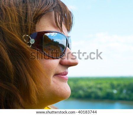 Portrait of the adult women in sunglasses against summer landscape