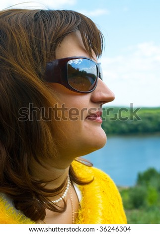 Portrait of the adult women in yellow against summer landscape