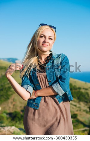 portrait of the attractive, slender, beautiful young Caucasian  blonde girl in a jeans jacket. Smiling girl enjoys fine warm sunner weather highly in mountains against the sea - stock photo