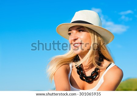 portrait of the attractive, slender, beautiful young Caucasian  blonde girl in a stinny hat. Smiling girl enjoys fine warm sunner weather highly in mountains - stock photo