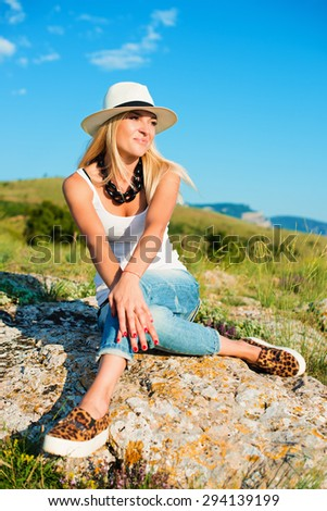portrait of the attractive, slender, beautiful young Caucasian  blonde girl in a stinny hat.Smiling girl enjoys fine warm sunner weather highly in mountains against the sea - stock photo