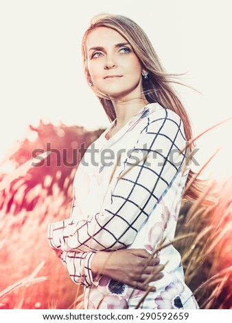 portrait of the attractive, slender, beautiful young Caucasian  blonde girl outdoor. Beautiful modern woman  with the long developing fair hair in a loose dress. dressy style. snub nose. - stock photo