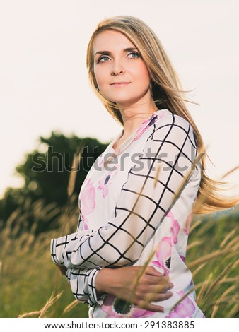 portrait of the attractive, slender, beautiful young Caucasian  blonde girl outdoor. Beautiful modern woman  with the long developing fair hair in a loose dress. dressy style. snub nose - stock photo