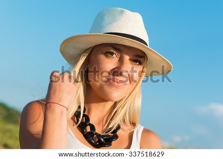 portrait of the attractive, slender, beautiful young Caucasian  blonde girl. Smiling girl enjoys fine warm summer weather highly in mountains against the sea - stock photo
